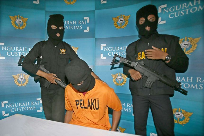 Customs officers guarding Singaporean Mohammad Noh Abdul Salam after he was arrested for drug possession in Bali's Ngurah Rai Airport, on April 27, 2016.