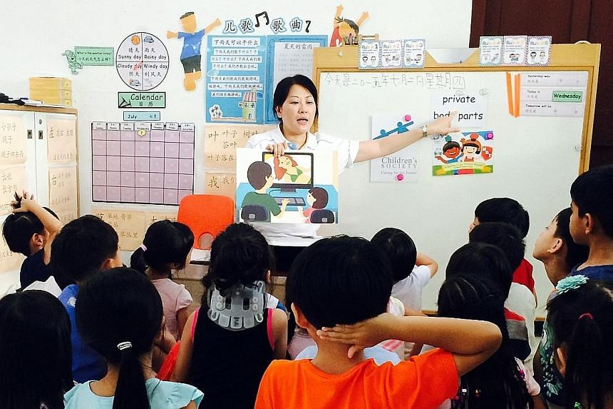 """A staff member of Singapore Children's Society conducting a KidzLive session. The society runs such sessions at pre-schools for free to teach five- and six-year-olds """"body safety skills""""."""