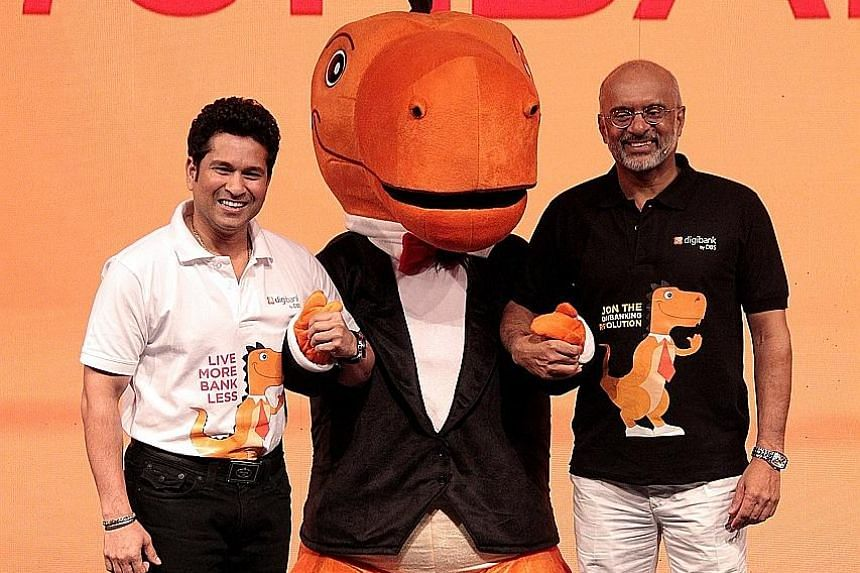 Cricket legend Sachin Tendulkar (left) and DBS Bank CEO Piyush Gupta at the launch of digibank. With them is dinosaur mascot Digor, who symbolises change and thriving in a digital age.