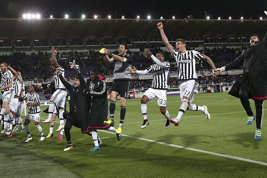 Jubilant Juventus players celebrate their 2-1 win over Fiorentina on Sunday. Napoli's loss to Roma on Monday meant that Juve are confirmed Serie A champions for a fifth straight season.