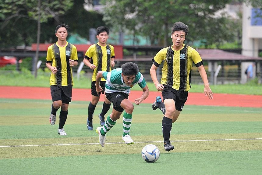 Raffles Institution's Jonathan Chua (green jersey) battling for possession against Temasek Junior College players during their 3-1 win yesterday, which ensured that RI move on to the Schools National A Division semi-finals.