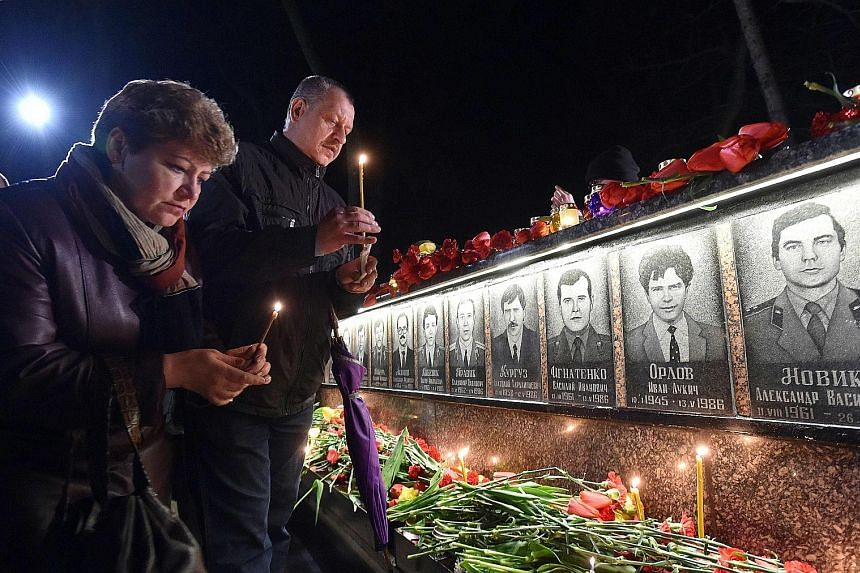 Above: A candle-lit memorial service was held yesterday in front of the monument to Chernobyl victims in Slavutych, some 50km from the accident site. Left: A protective shelter over the remains of nuclear reactor Unit 4 is under construction.