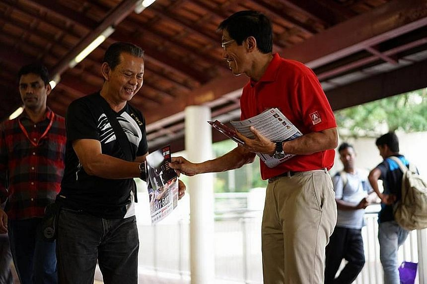 Dr Chee Soon Juan, SDP's candidate for the Bukit Batok by-election, greeting a resident near Bukit Batok MRT station. He spent the Nomination Day eve distributing fliers and greeting commuters at the station.