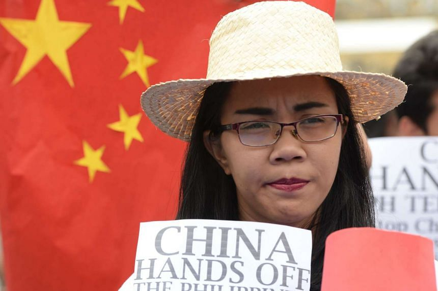 A Filipino student holding anti-Chinese placards during a rally in Manila on March 3.