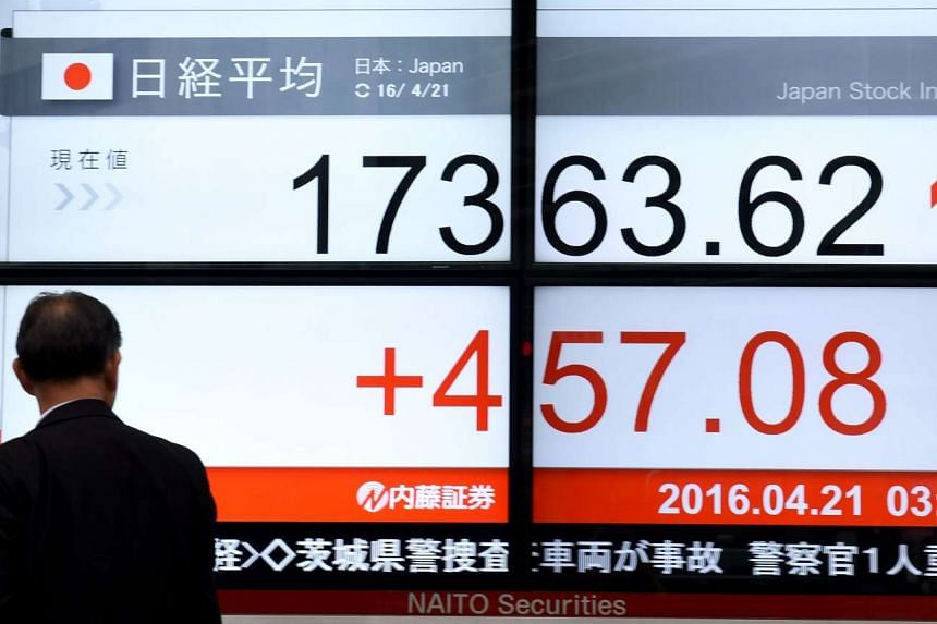 A businessman looks at the electronic stock indicator outside a security company in Tokyo.