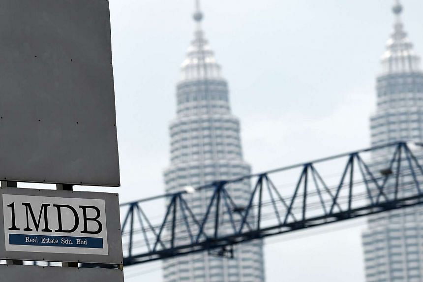 Malaysia's iconic twin towers are seen in the backdrop of the 1MDB logo on a billboard at the funds flagship Tun Razak Exchange site in Kuala Lumpur.