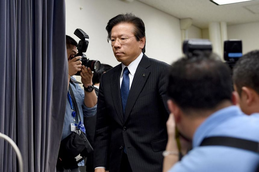Mitsubishi Motors president and COO Tetsuo Aikawa (centre) entering the room to start his press conference at the transport ministry in Tokyo on April 26, 2016.