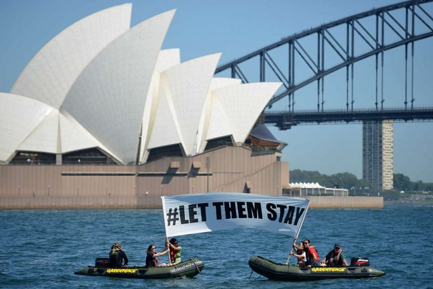 """Members of the environmental group Greenpeace holding a sign that reads """"#LET THEM STAY"""" in front of the Sydney Opera House on Feb 14."""