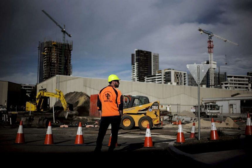 A worker standing in front of a construction site for new apartment blocks in Sydney on June 24, 2015.