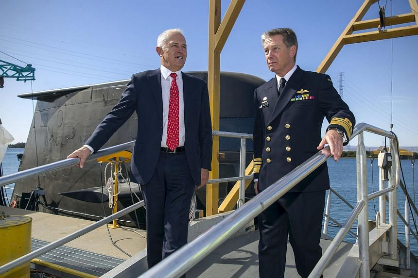 Mr Turnbull (left) disembarking an Australian submarine with Navy Vice-Admiral Timothy Barrett in Adelaide on April 26.