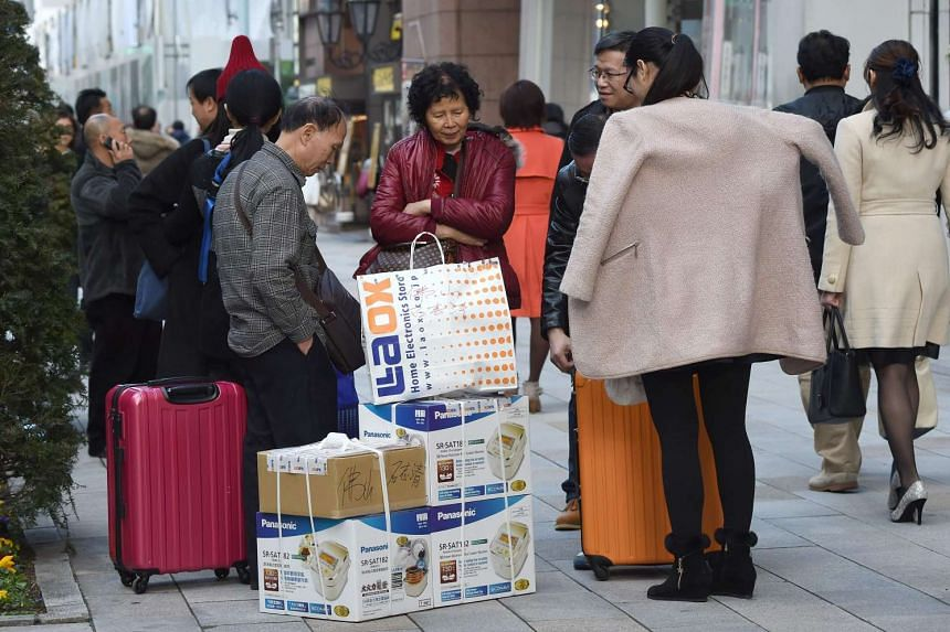 Foreign tourists collecting their souvenirs on the street after shopping in Tokyo.