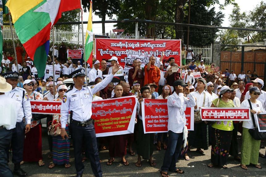 Buddhist monks and nationalists hold flags and placards in front of the US embassy in Yangon during a demonstration on April 28, 2016.