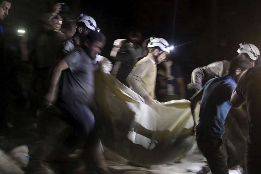 Civil defence members carry a casualty after an airstrike at a field hospital in the rebel held area of al-Sukari district of Aleppo, Syria on April 27, 2016.