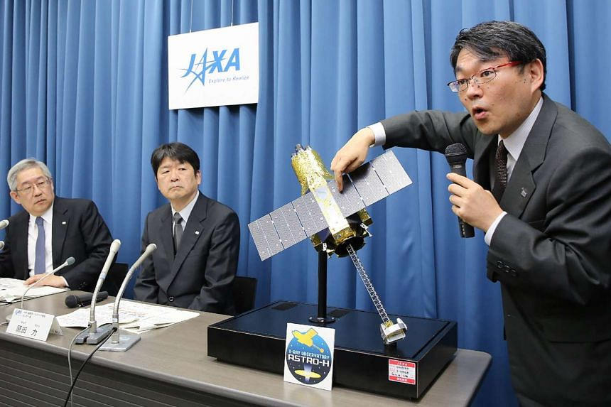 Takashi Kubota (right), space program director of the Japan Aerospace Exploration Agency, answers questions during a press conference in Tokyo on April 28, 2016.