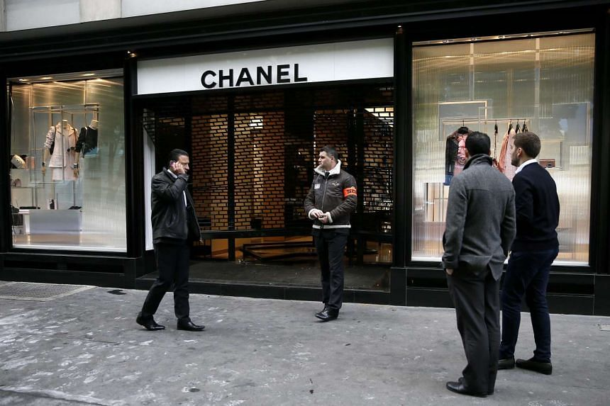 A security member stands guard outside the Chanel store along Avenue Montaigne after a car smashed into the front windows, in Paris, France on April 28, 2016.