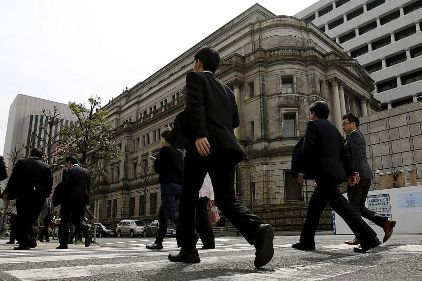 Businessmen walk past the Bank of Japan (BOJ) building in Tokyo, Japan, on March 23, 2016.