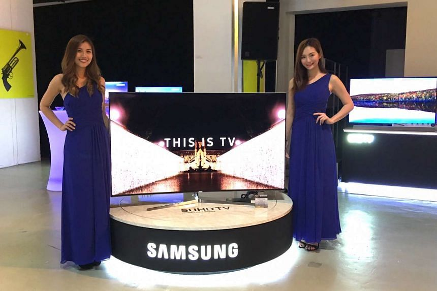 Models posing with the latest Samsung SUHD TV during a media event at Red Dot Museum.