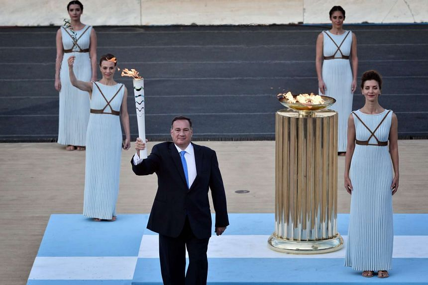 Hellenic Olympic Committee President Spyros Kapralos (centre) holds the torch with the Olympic flame prior to passing it to the Rio 2016 organising committee president during the handover ceremony in Athens.