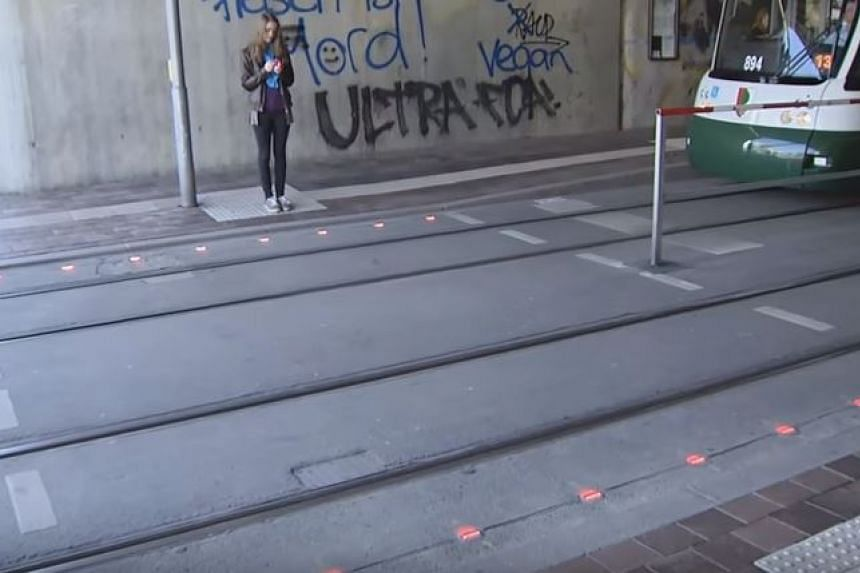 Flashing traffic lights installed on the sidewalk in Augsburg, Germany.