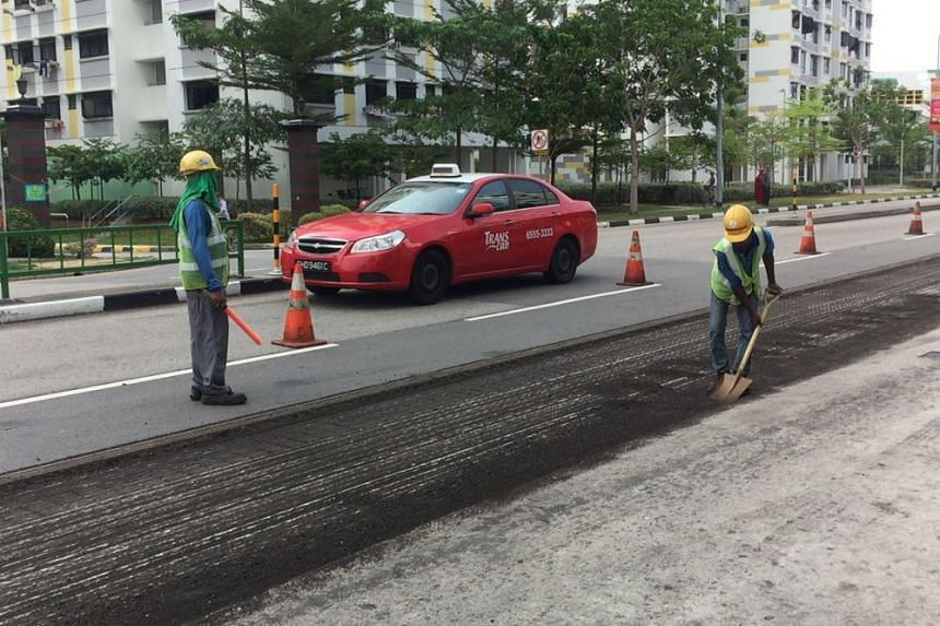 Workers conducting clean-up efforts along Tampines Avenue 9, where the oil spill occurred.