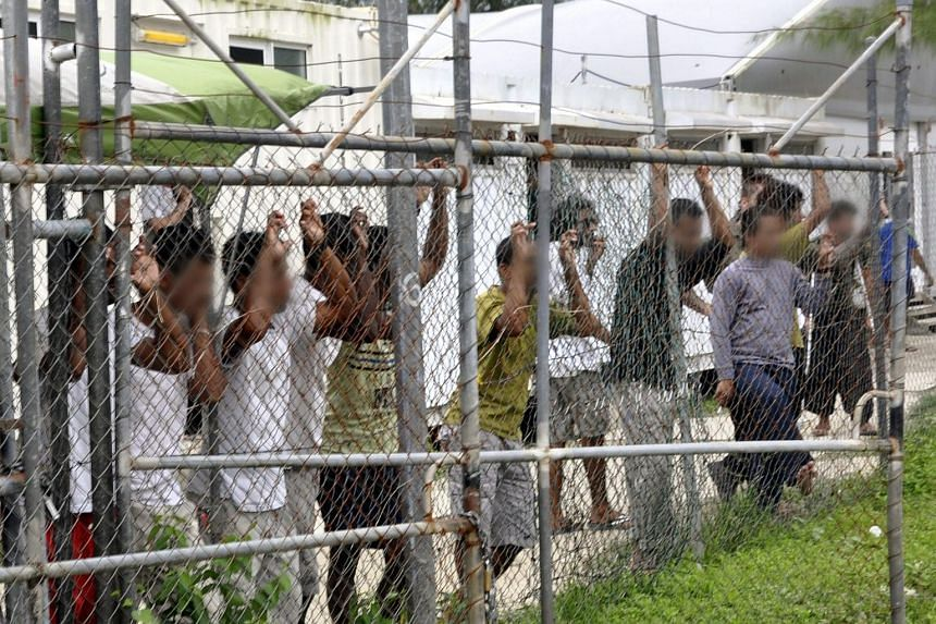 Asylum seekers staring at media from behind a fence at the Oscar compound in the Manus Island detention centre, Papua New Guinea.
