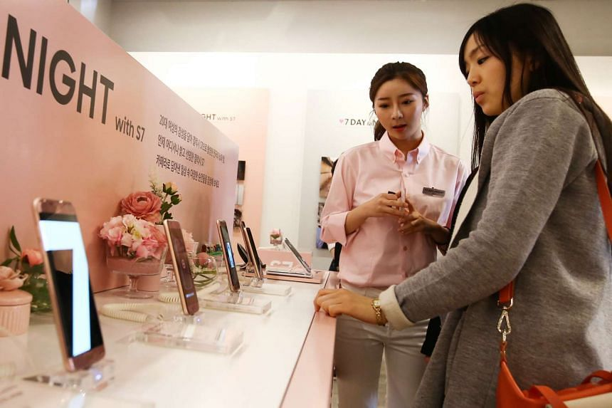 An employee (left), assists a customer as she looks at Samsung Electronics Co. Galaxy S7 and S7 Edge smartphones.