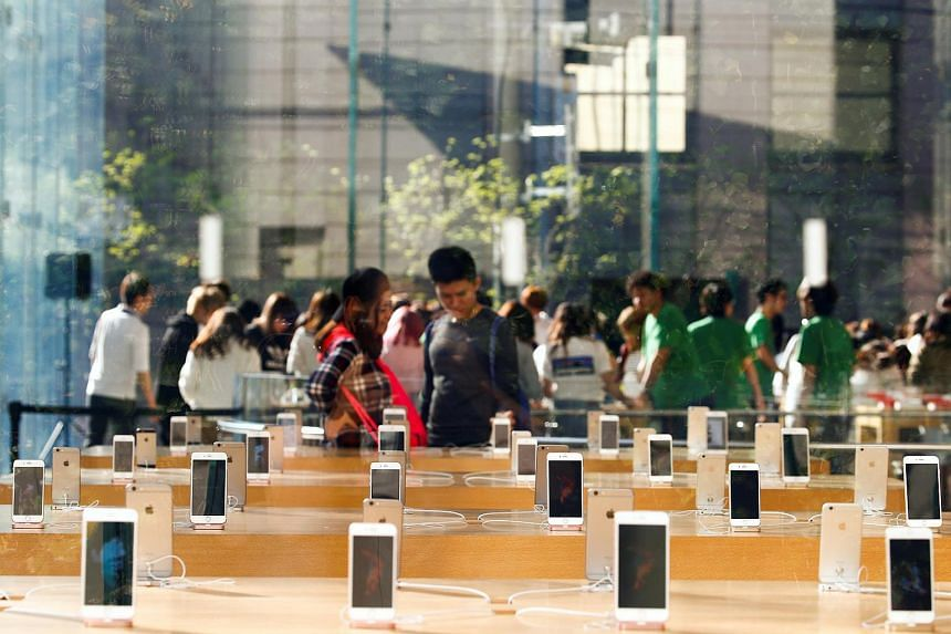 People look at smartphones at an Apple store in Tokyo.