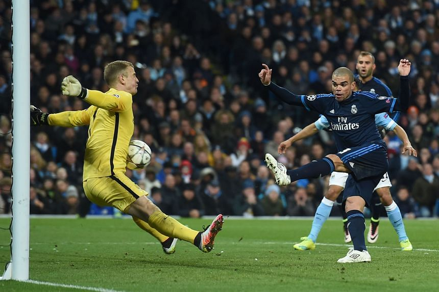 Manchester City's Joe Hart (left) shows he can stomach any challenge as he makes an unconventional save against Real's Pepe during the Champions League semi-final first leg 0-0 draw on Tuesday.