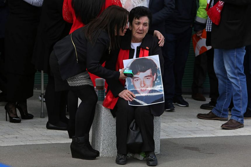 A woman holds an image of one of the 96 victims of the 1989 Hillsborough disaster, as she reacts after the coroner's court in Warrington, north-west England, ruled that the fans were unlawfully killed through errors in police planning.