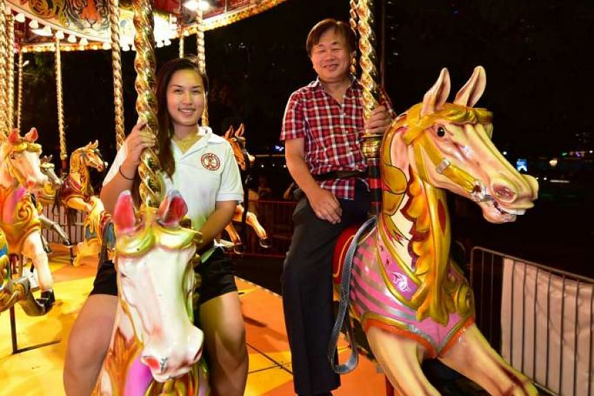 Mr Lee, better known as Uncle Ringo, on a horse carousel with his daughter Joyce, who is the company's sales and marketing manager. Mr Lee started the funfair in 1984, the same year his daughter was born.