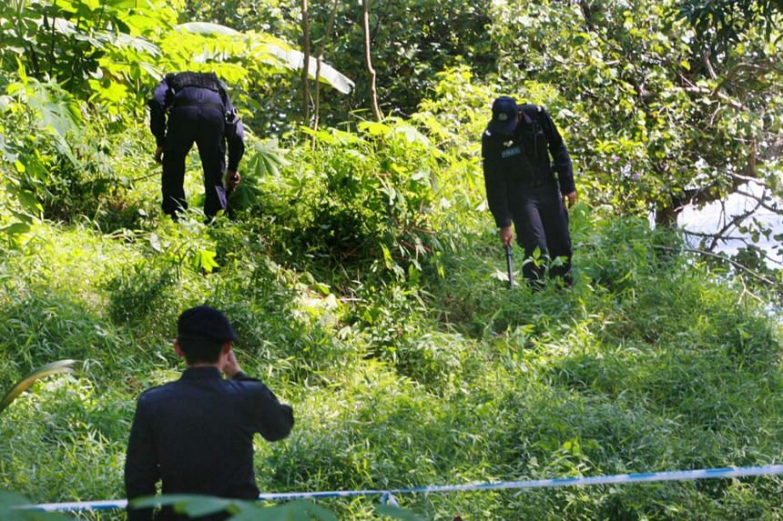 Police at a forested area near Sembawang Beach, where the body of taxi driver Yuen Swee Hong, 58, was found.