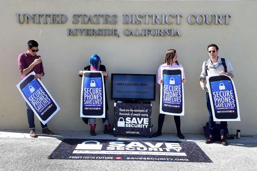 """Activists hold placards reading """"Secure Phones Saves Lives"""" during a protest in front of the US District Court in California in March. The FBI has refused to share details on how it unlocked an attacker's iPhone."""