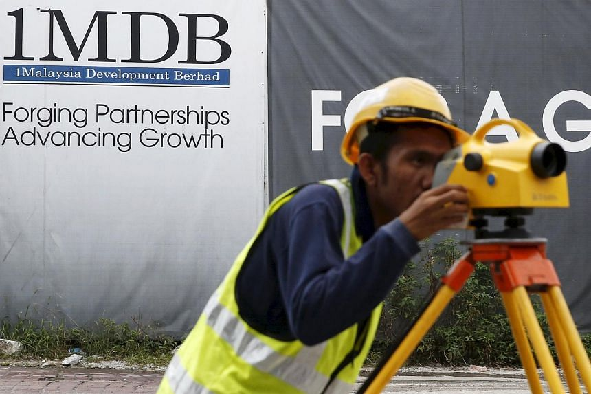 A construction worker working in front of a 1MDB billboard at the Tun Razak Exchange development in Kuala Lumpur, Malaysia on Feb 3, 2016.