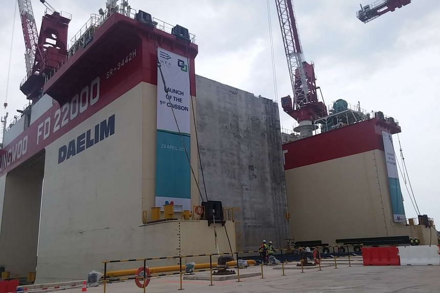 The first caisson, the concrete block in the middle, was launched on April 29, 2016, at the Tuas Terminal.