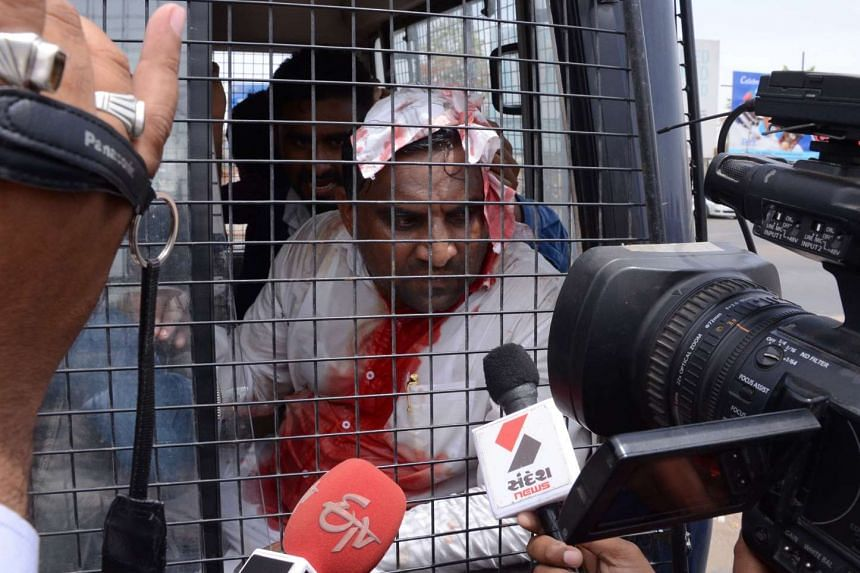 Indian Patel Patidar Community leader Laljibhai Patel sits in a police van after he was injured in clashes between supporters of Patel Patidar and Gujarat Police, on April 17, 2016.