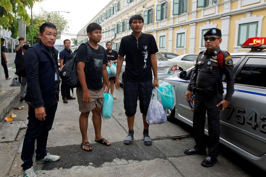 Police officers escorts three of the eight people charged with sedition and computer crimes as they arrive at the military court in Bangkok, on April 29, 2016.