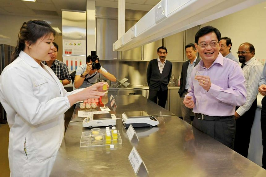 Research officer Wang Nan Xin (left) preparing a sugar sample for Minister for Finance Mr Heng Swee Keat to taste.