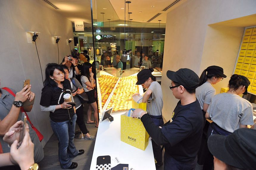 Staff packing tarts for customers at the opening of Bake Cheese Tarts at Ion Orchard on April 29, 2016.