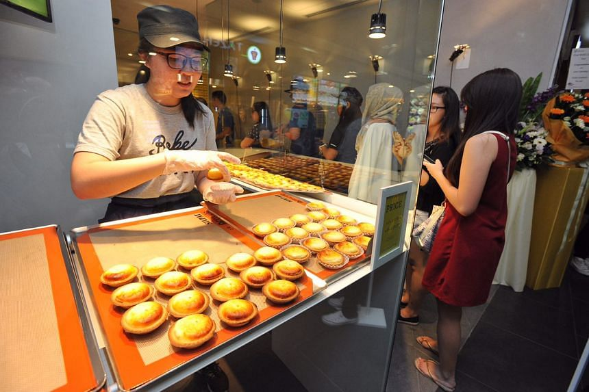 A staff preparing the tarts at the opening of Bake Cheese Tarts at Ion Orchard on April 29, 2016.