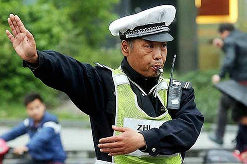 Minutes after Mr Li (below) diverted vehicles in Hangzhou last Thursday, the crack widened and became a sinkhole that could have easily swallowed three cars. Mr Li, an auxiliary traffic police officer, has been nominated for a first-class public secu