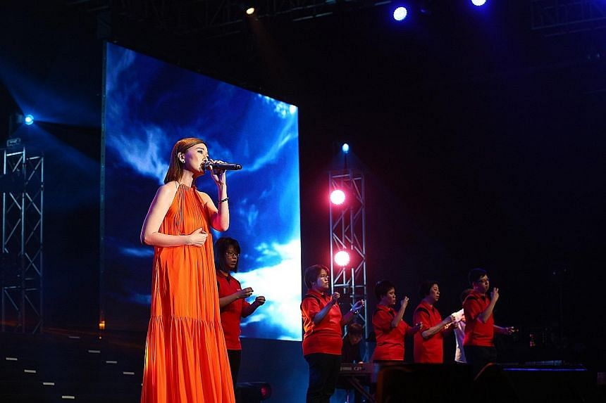 Singer Joi Chua performing with members of the Touch Silent Club at the Care & Share Thank You concert at Singapore Expo yesterday. The movement exceeded expectations in the amount raised.