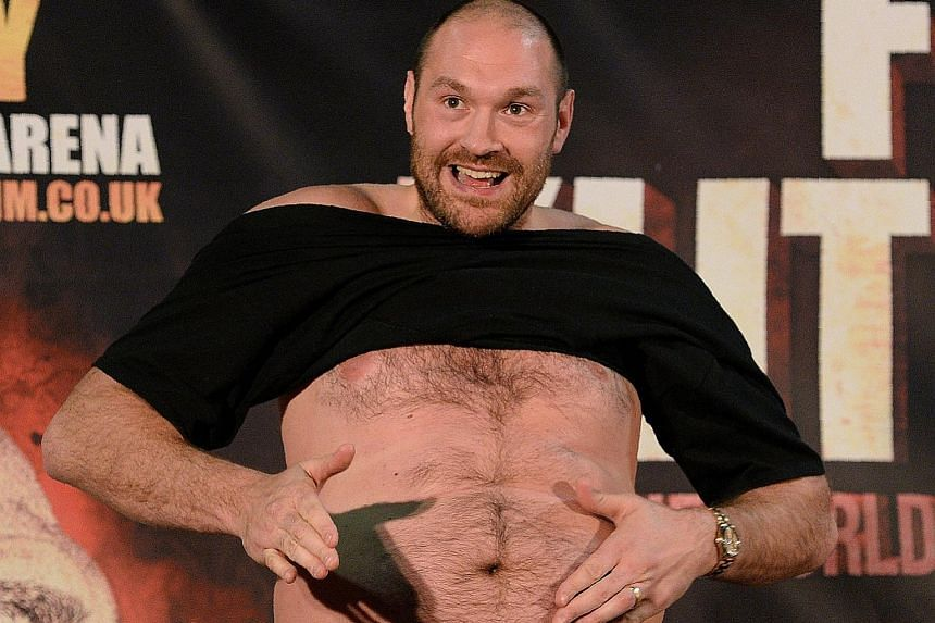 British world heavyweight champion Tyson Fury shows off his flab at a press conference in Manchester on Wednesday while taunting Wladimir Klitschko of Ukraine before their world title re-match in July.