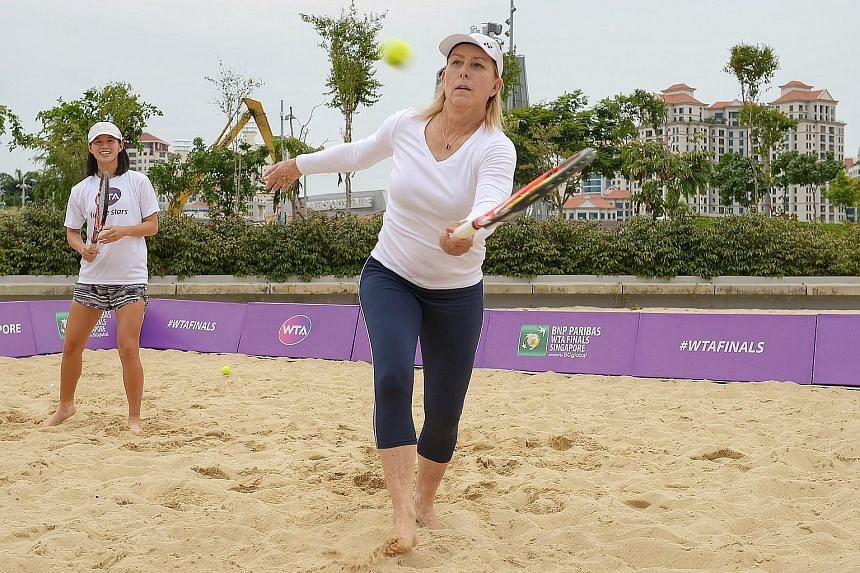 Tennis legend Martina Navratilova (right) hits a volley on a makeshift beach outside the Singapore Sports Hub. Her doubles partner yesterday was national junior player Ashley Yim.