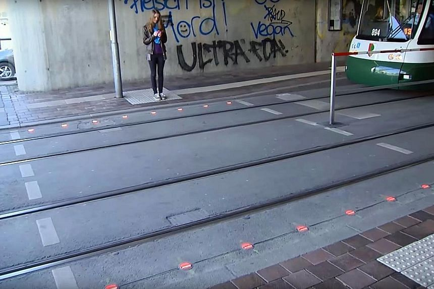 The authorities in Augsburg recently installed the in-ground traffic lights at crossings in two crowded train stations. The flashing lights are to warn pedestrians who are busy looking at their phones against stepping onto the road.