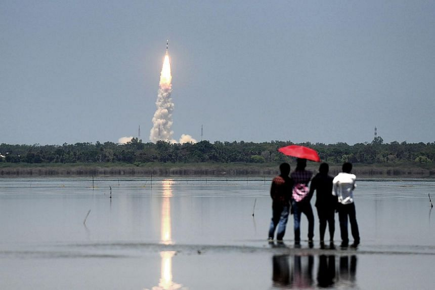 Bystanders looking on as Indian Space Research Organisation's navigation satellite IRNSS-1G, on board the Polar Satellite Launch Vehicle (PSLV-C33) is launched from Sriharikota in the southern Indian state of Andhra Pradesh on April 28, 2016.