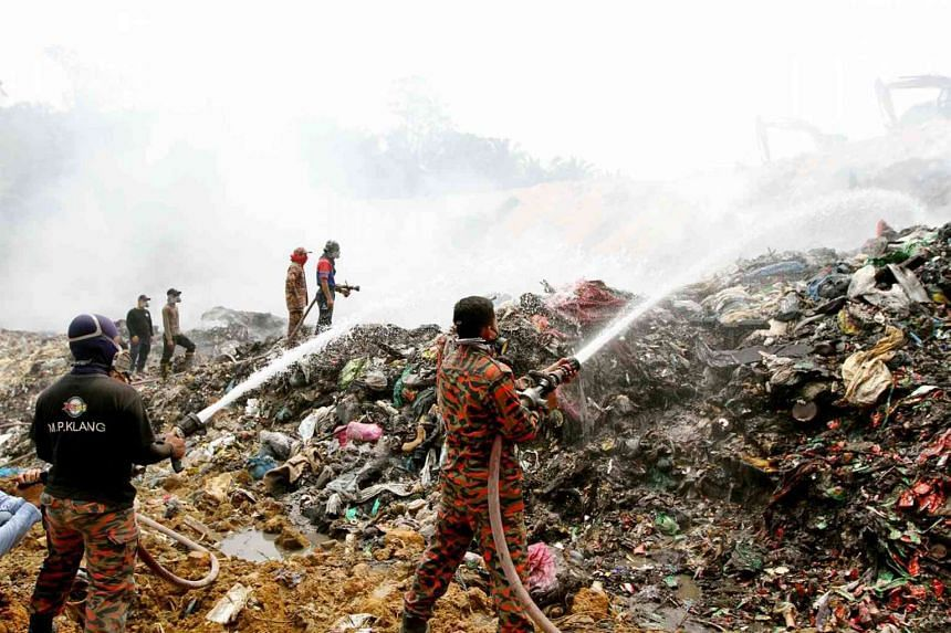 Firefighters putting out blazes at an illegal waste dump in Klang, Malaysia.