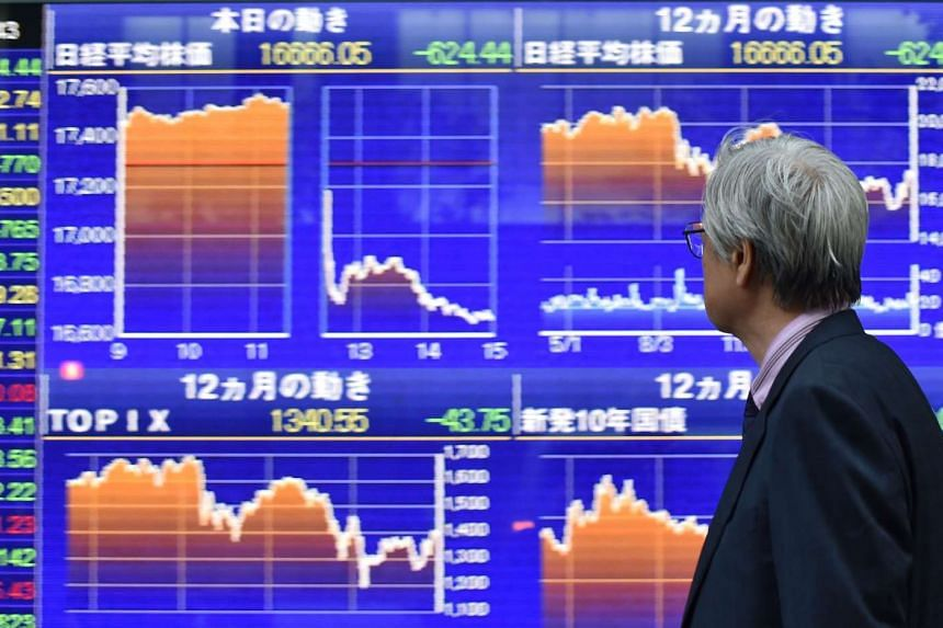 A man looking at a quotation board flashing the Nikkei key index from the Tokyo Stock Exchange in Tokyo on April 28, 2016.