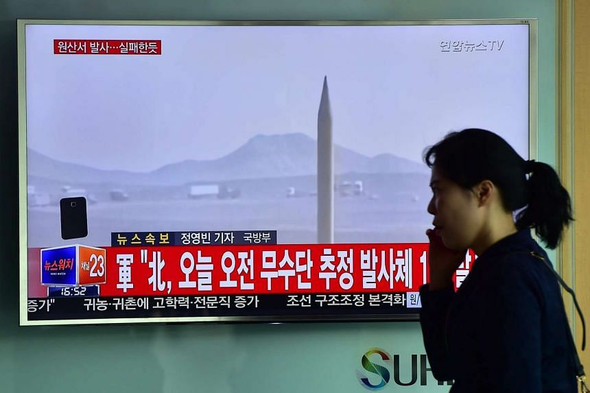A woman walks past a TV screen showing a file footage of a North Korean missile launch at a railway station in Seoul, on April 28, 2016.