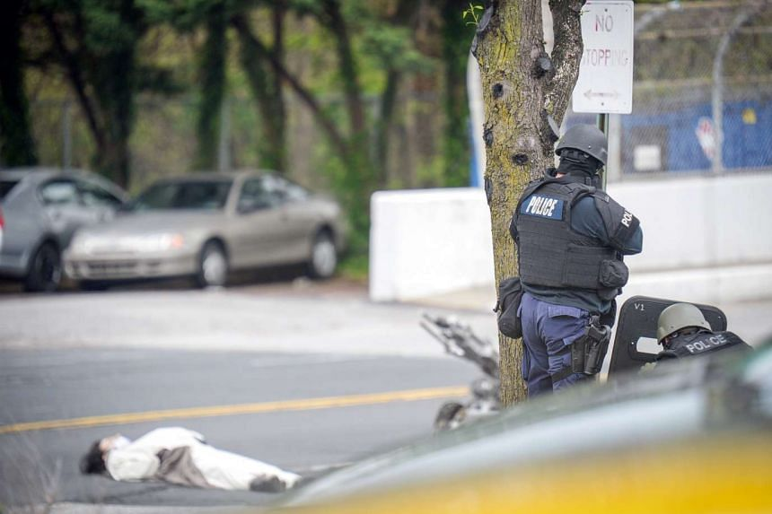 A man, claiming to have a bomb, lays in the street outside of the Fox45 television station in Baltimore, Maryland on Tuesday.