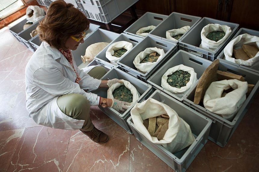 A woman opening a bag filled with Roman era bronze coins at Seville's Archeology Museum on April 28.